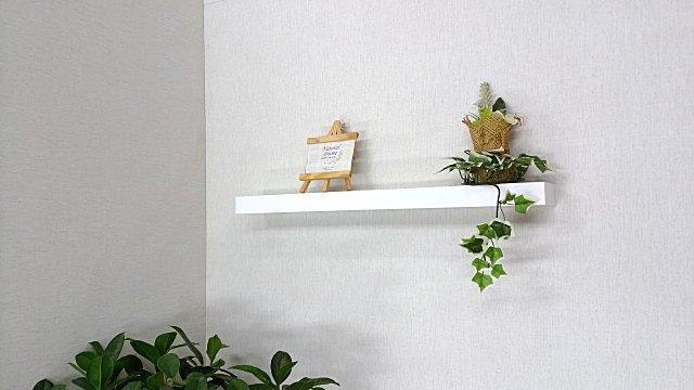 クロスの壁にピン止めの棚板