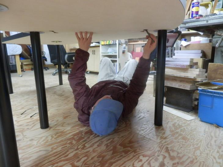 連結ボルトの締め付けは天板の下に潜り込んで取り付けます