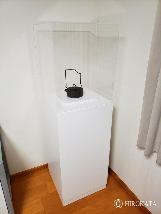 アクリルケースを載せた白い展示台