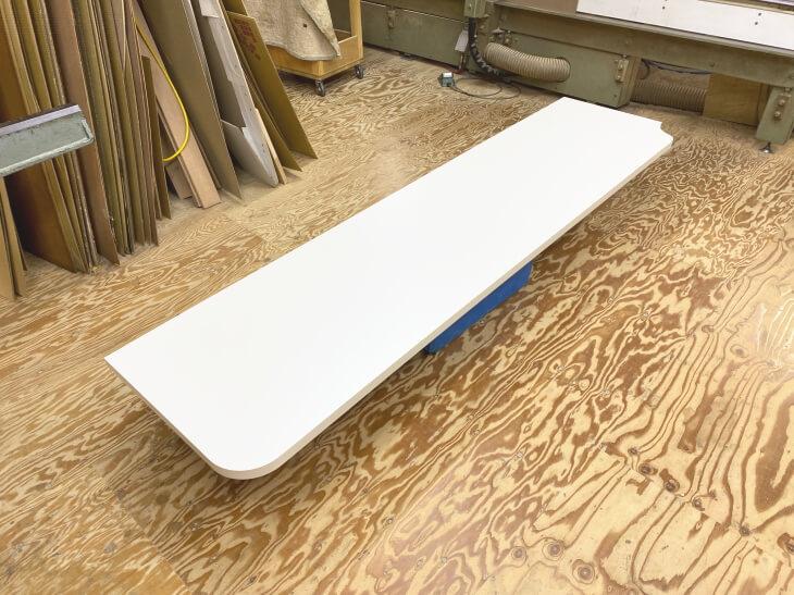 カーテンをかわす切り欠き加工のカウンターテーブル天板